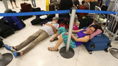 In this Monday, Sept. 25, 2017 photo, stranded passengers rest in the main international airport in the aftermath of Hurricane Maria, in San Juan, Puerto Rico. (AP Photo/Gerald Herbert)