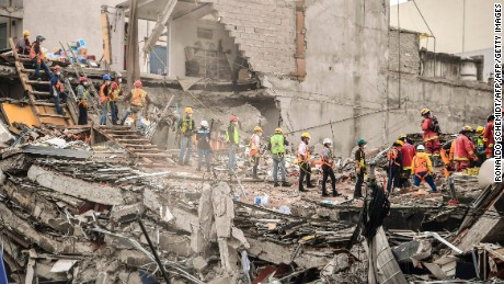 Volunteers help as rescuers (R) still search for victims in a building toppled by a magnitude 7.1 quake that struck central Mexico a week ago, in Mexico City on September 26, 2017.  A week after an earthquake that killed more than 300 people, a shaken Mexico was torn Tuesday between trying to get back to normal and keeping up an increasingly hopeless search for survivors. / AFP PHOTO / Ronaldo SCHEMIDT        (Photo credit should read RONALDO SCHEMIDT/AFP/Getty Images)