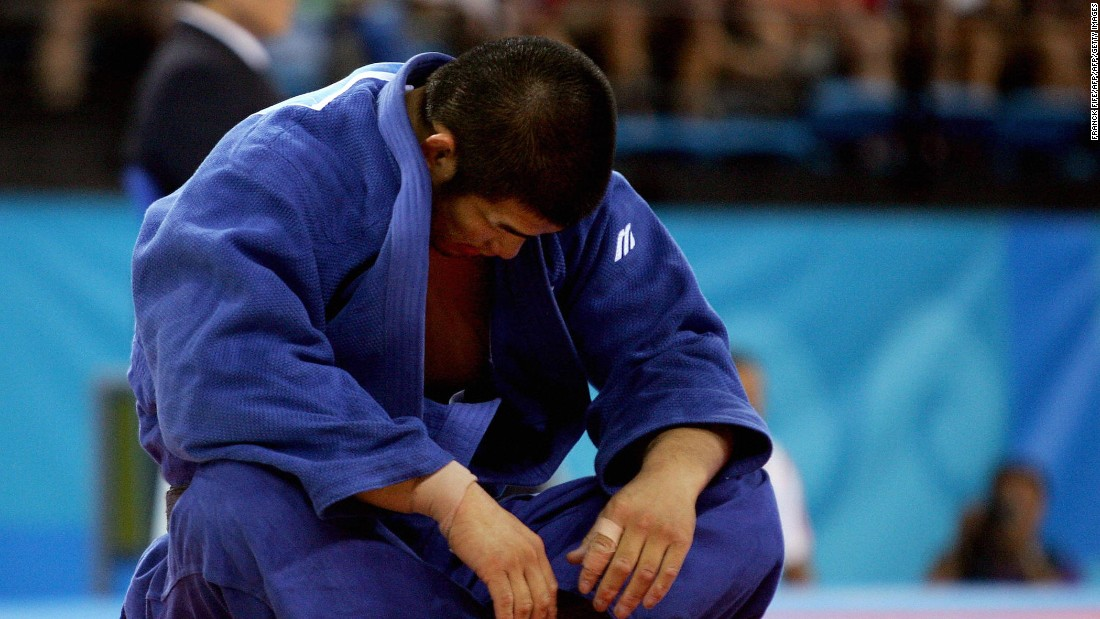 Inoue sits dejected after a loss to Dutch opponent Elco van Der Geest in men's -100 kg competition at the Athens 2004 Olympic Games.