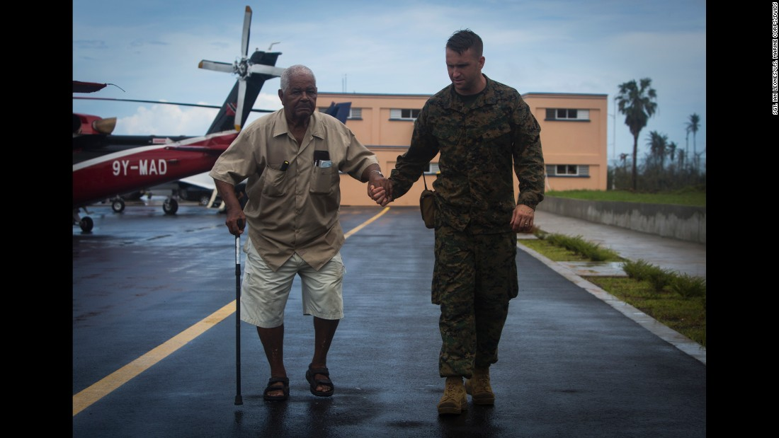 Marine Gunnery Sgt. Philip C. Sackett escorts a US citizen to an evacuation control center at the Douglas-Charles Airport in Dominica on Sunday, September 24. The control center was set up to help people who were stranded on the island after Hurricane Maria.