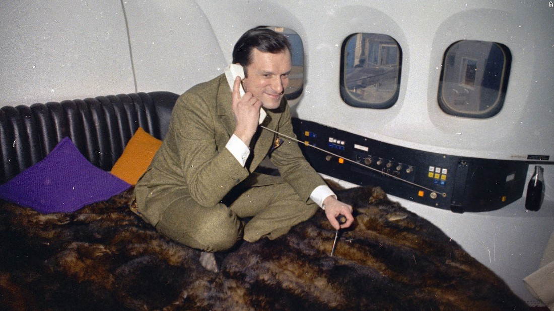 Hefner is seen taking a phone call aboard his private plane in 1970.