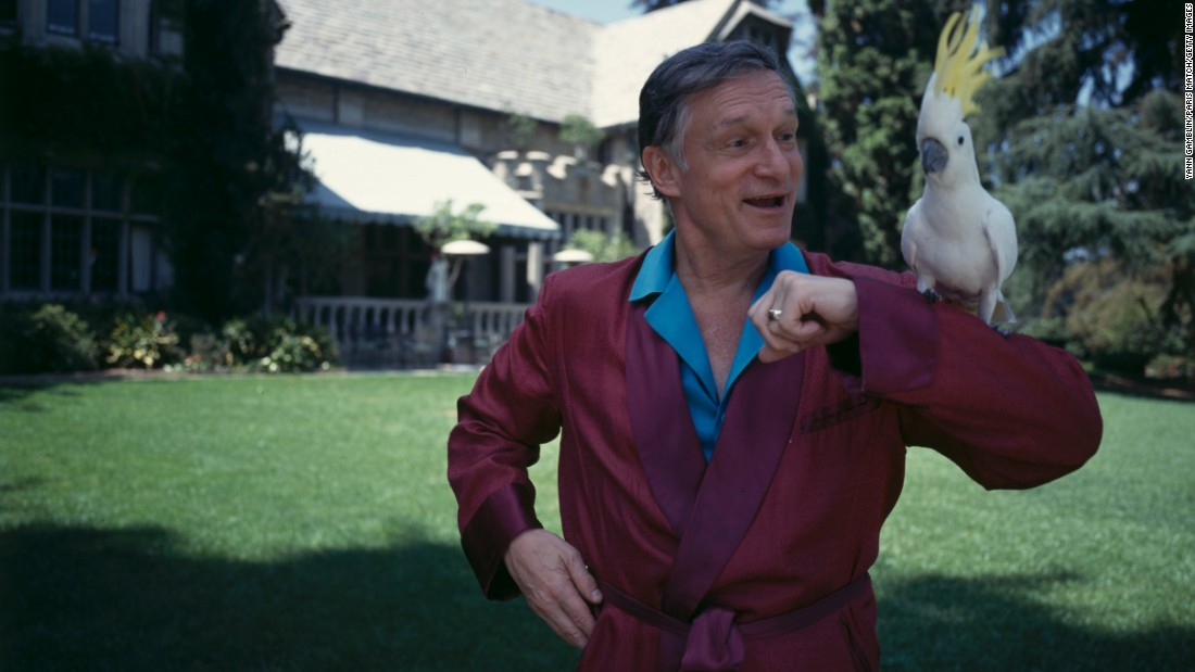 Hefner poses with a cockatoo in one of his iconic silk robes at the Playboy Mansion in November 1993.