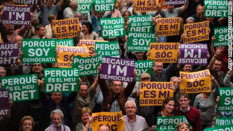 "Attendees hold posters reading ""Because I'm democrat"" and ""Because it's my right"" during a political rally supporting a referendum on independence, at the Catalonia's Congress Palace of Catalonia in Barcelona on May 19, 2017.  Spain's conservative government today urged Catalan president Carles Puigdemont to present his proposal to hold a regional independence referendum before parliament instead of in public.   / AFP PHOTO / Josep LAGO        (Photo credit should read JOSEP LAGO/AFP/Getty Images)"