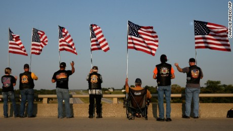 People hold flags and wave at passing vehicles to remember the anniversary of the Sept. 11 terrorist attacks from an overpass on Interstate 35 Monday, Sept. 11, 2017, near Melvern, Kan. Area residents began manning the bridge on the anniversary in 2002 and have done it every since drawing about 300 people throughout the day. (AP Photo/Charlie Riedel)