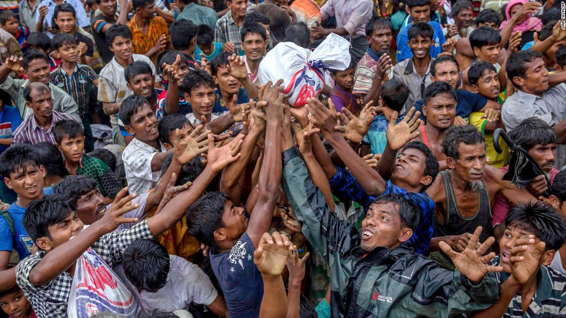 People scramble to catch food distributed by aid groups on September 18, at the Balukhali refugee camp in Bangladesh.
