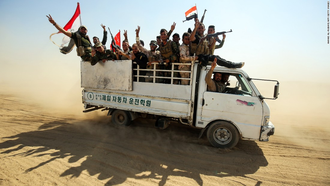 Fighters of the Hashed al-Shaabi, or Popular Mobilization Units, flash the victory sign while advancing toward the northern Iraqi town of Sharqat on Friday, September 22.