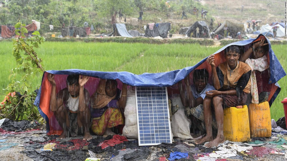 Rohingya refugees take cover from monsoon rains on September 17, in the Balukhali refugee camp in Bangladesh.