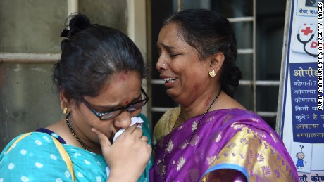 Indian relatives of victims injured at a stampede on a railway bridge react as they wait at a hospital in Mumbai on September 29, 2017.