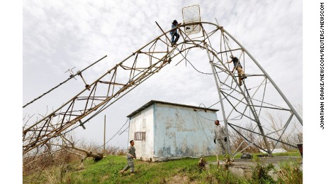 A radio station engineer removes needed equipment from a tower mangled by Hurricane Maria last week, as soldiers from the U.S. Army's Civil Authority Information Support Element assist below, on St. Croix, U.S. Virgin Islands Tuesday, September 26.