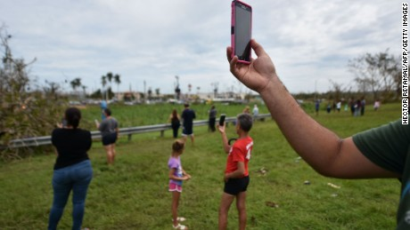People try to get a cellphone signal in Dorado, 40 km north of San Juan, Puerto Rico, on September 23. Communications, electric power, water supply and the lack of gas have been seriously affected after the passage of Hurricane Maria.