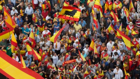 People wave Spanish  flags as thousands demonstrate Saturday in Madrid in favor of national unity.