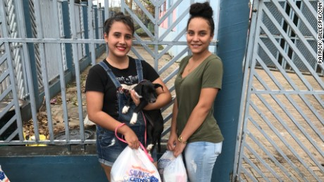 Eyleen Gonzalez with her stepsister, Amathys Santana, and her puppy, Lena, after receiving food from Daddy Yankee in Toa Baja, Puerto Rico.