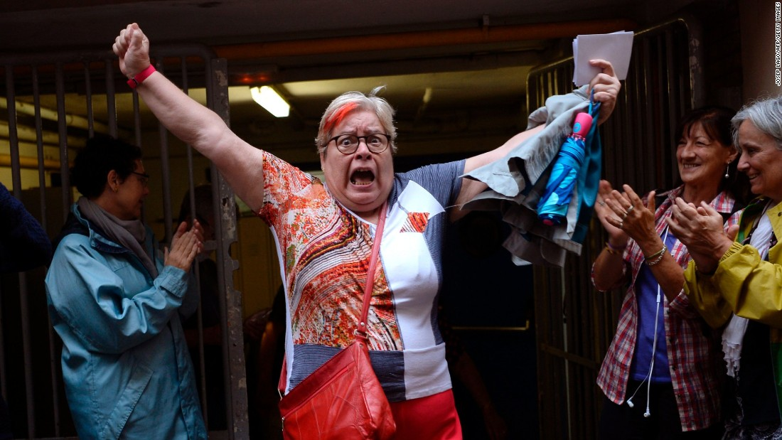A woman celebrates outside a polling station after casting her vote in Barcelona, on October 01 in a referendum on independence for Catalonia.