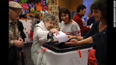 BARCELONA, SPAIN - OCTOBER 01:  A woman casts her vote into the ballot box at a polling station as voting continues in the referendum on October 1, 2017 in Barcelona, Spain. More than five million eligible Catalan voters are estimated to visit 2,315 polling stations today for Catalonia's referendum on independence from Spain. The Spanish government in Madrid has declared the vote illegal and undemocratic.  (Photo by Dan Kitwood/Getty Images)