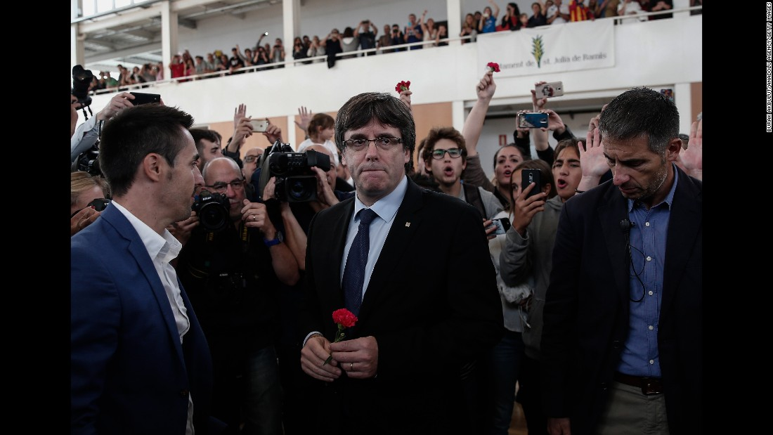 "Catalan President Carles Puigdemont, center, arrives to inspect a sports hall as police interve in Girona, Spain. Puigdemont condemned ""indiscriminate aggression"" against peaceful voters."