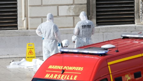 Police stand over a body after a man stabbed two women to death on Sunday at a train station in Marseille, France.