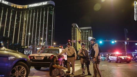 Police officers stand at the scene of a shooting near the Mandalay Bay resort and casino on the Las Vegas Strip, Sunday, October 1, 2017, in Las Vegas. Multiple victims were being transported to hospitals after a shooting late Sunday at a music festival on the Las Vegas Strip.