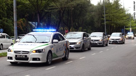Police cars carrying the two suspects enter the Shah Alam court house outside Kuala Lumpur, Malaysia on Monday, Oct. 2.