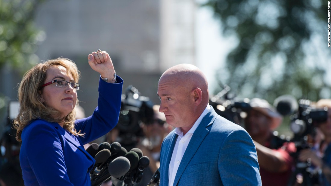 Former US Rep. Gabrielle Giffords -- accompanied by her husband, Mark Kelly -- turns to shake her fist at the Capitol during a news conference on October 2. Giffords, who was shot by a constituent in 2011, has been calling on Congress to do more to address gun violence.