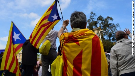 People hold Catalan pro-independence 'Estelada' flags as they raise their fists during a protest in Barcelona, on October 2, 2017 a day after hundreds were injured in a police crackdown during Catalonia's banned independence referendum. Catalonia's leader Carles Puigdemont said the region had won the right to break away from Spain after 90 percent of voters taking part in a banned referendum voted for independence, defying a sometimes violent police crackdown and fierce opposition from Madrid. / AFP PHOTO / PIERRE-PHILIPPE MARCOU        (Photo credit should read PIERRE-PHILIPPE MARCOU/AFP/Getty Images)