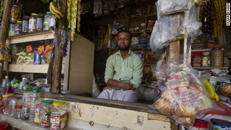 Salimullah, a Rohingya refugee who fled Myanmar in 2003, sits in front of the general store he now owns and operates in the Kanchan Kunj Rohingya settlement in New Delhi, India.