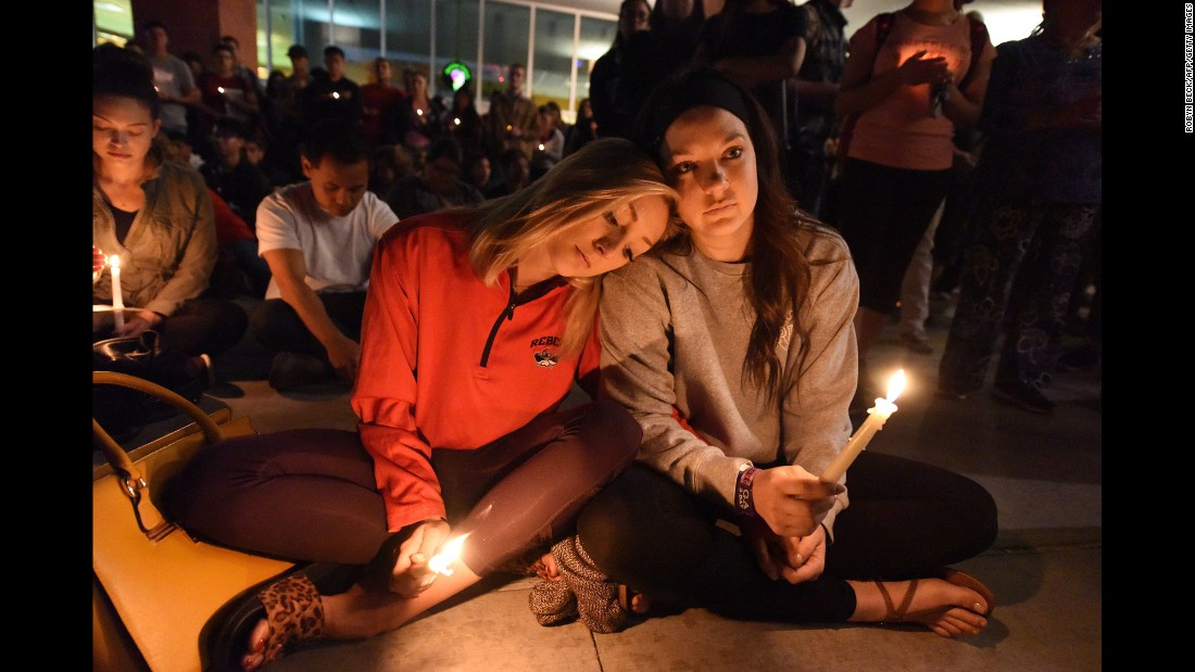 Lindsay Cotterman rests her head on Shawna Pieruschka's shoulder as they attend a candlelight vigil at the University of Nevada, Las Vegas on Monday, October 2.