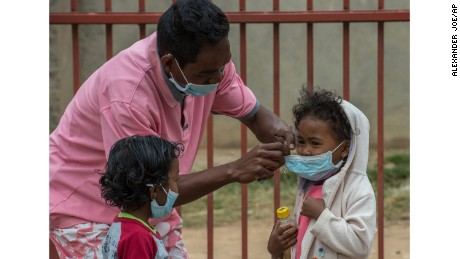 Face masks are placed on children in Antananarivo, Madagascar, Tuesday, October 3.  Authorities in Madagascar are struggling to contain an outbreak of plague that has killed at least two dozen people, and the government has begun a campaign to disinfect school classrooms in the city.