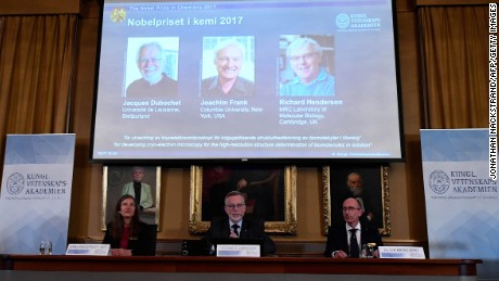 Members of the Nobel Committee (L-R) Sara Snogerup Linse, the Secretary General of the Royal Swedish Academy of Sciences Goran Hansson and Peter Brezezinski sit in front of a giant screen displaying the winners of the 2017 Nobel Prize in Chemistry (L-R) Jacques Dubochet from Switzerland, Joachim Frank from the US and Richard Henderson from Britain on October 4, 2017 at the Royal Swedish Academy of Sciences in Stockholm, Sweden. / AFP PHOTO / Jonathan NACKSTRAND        (Photo credit should read JONATHAN NACKSTRAND/AFP/Getty Images)