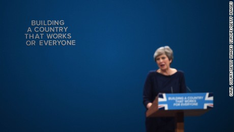An 'F' falls off the backdrop as British Prime Minister Theresa May delivers her keynote speech.
