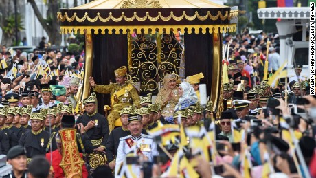 The Sultan and Queen Saleha wave from the royal chariot during the procession.