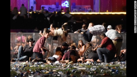 People scramble for shelter at the Route 91 Harvest country music festival. The shooter's motive remains a mystery.