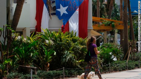 """Together as One"" reads on a torn Puerto Rican Flag hanging from a hotel in the tourist zone of el Condado in San Juan, Puerto Rico on October 4, 2017.  US President Donald Trump asks Congress for a bumper $29 billion package of emergency relief after Hurricane Maria slammed into Puerto Rico. / AFP PHOTO / Ricardo ARDUENGO        (Photo credit should read RICARDO ARDUENGO/AFP/Getty Images)"