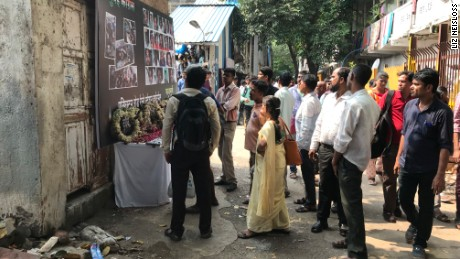 Commuters pause to look at photos of the stampede victims at Prabhadevi station, formerly known as Elphinstone station.