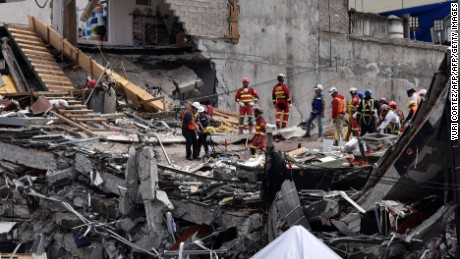 TOPSHOT - Rescuers dig through the rubble looking for victims in one of the buildings crushed during the September 19 earthquake in Mexico City, on October 1, 2017. More than a week after an earthquake that killed over 300 people, a shaken Mexico was torn between trying to get back to normal and keeping up an increasingly hopeless search for survivors. / AFP PHOTO / YURI CORTEZ        (Photo credit should read YURI CORTEZ/AFP/Getty Images)