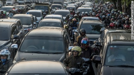 Commuters wait in a traffic jam during afternoon rush hour in Jakarta on September 8, 2017.