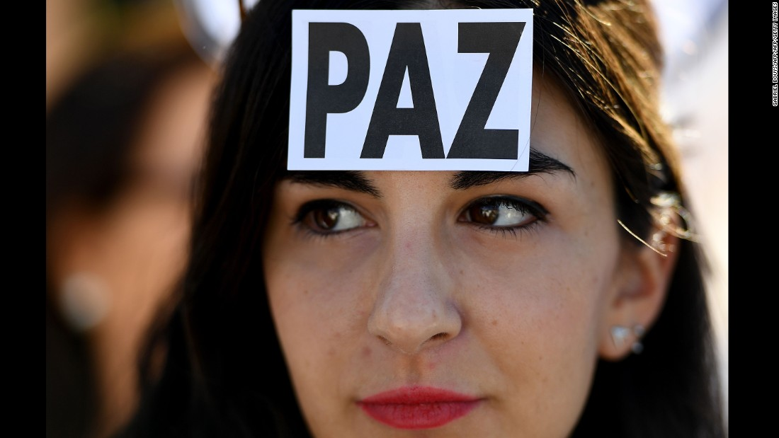 "A woman wears a sticker with the Spanish word for ""peace"" at a demonstration in Madrid on October 7."