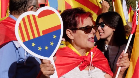 A woman takes part in a pro-unity march in Barcelona on October 8, 2017, with a heart bearing the flags of Catalonia, Spain and the European Union.
