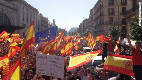 Protesters wave Spanish, Catalan and European Union flags in a call for unity on October 8, 2017, in Barcelona, Spain.