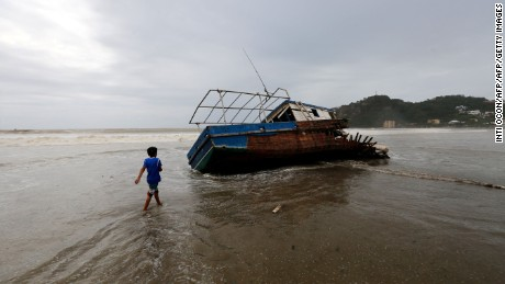 TOPSHOT - A boy walks towards a stranded boat in San Juan del Sur beach, following the passage of Tropical Storm Nate, in Rivas some 140km from Managua, Nicaragua, on October 6, 2017 Tropical Storm Nate gained strength as it headed toward popular Mexican beach resorts and ultimately the US Gulf coast after dumping heavy rains in Central America that left at least 22 people dead. / AFP PHOTO / INTI OCON        (Photo credit should read INTI OCON/AFP/Getty Images)