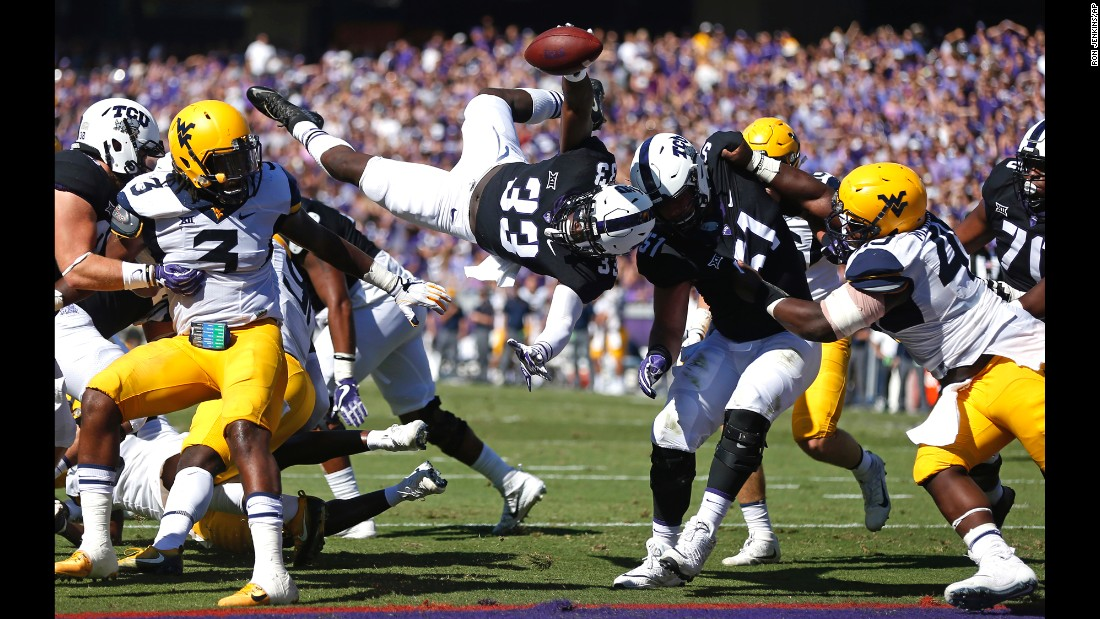 TCU running back Sewo Olonilua, center, dives over the goal line to score a touchdown against West Virginia on Saturday, October 7, in Fort Worth, Texas. TCU defeated West Virginia 31-24.