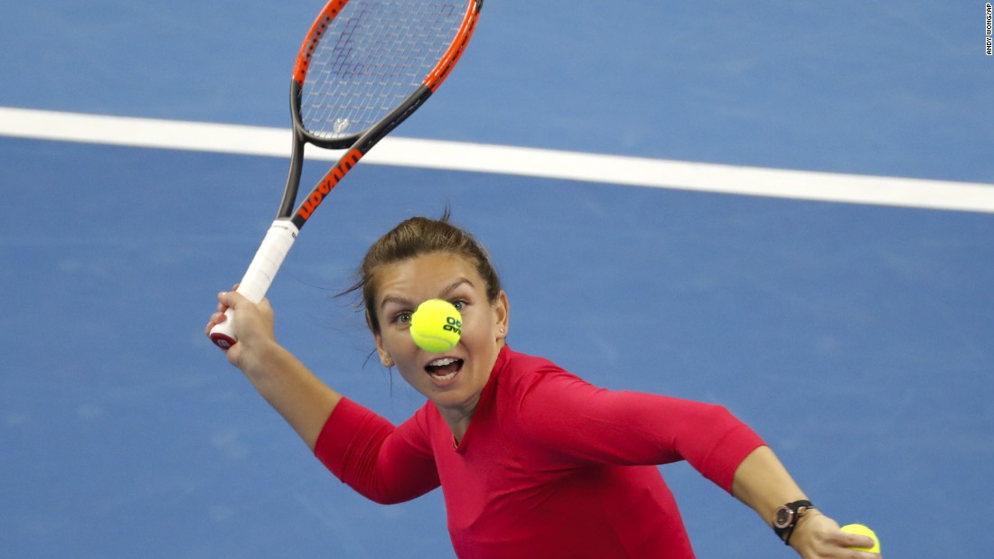 Simona Halep of Romania eyes a ball to hit to the spectators after defeating Maria Sharapova in their women's singles match of the China Open tennis tournament in Beijing on Wednesday, October 4.