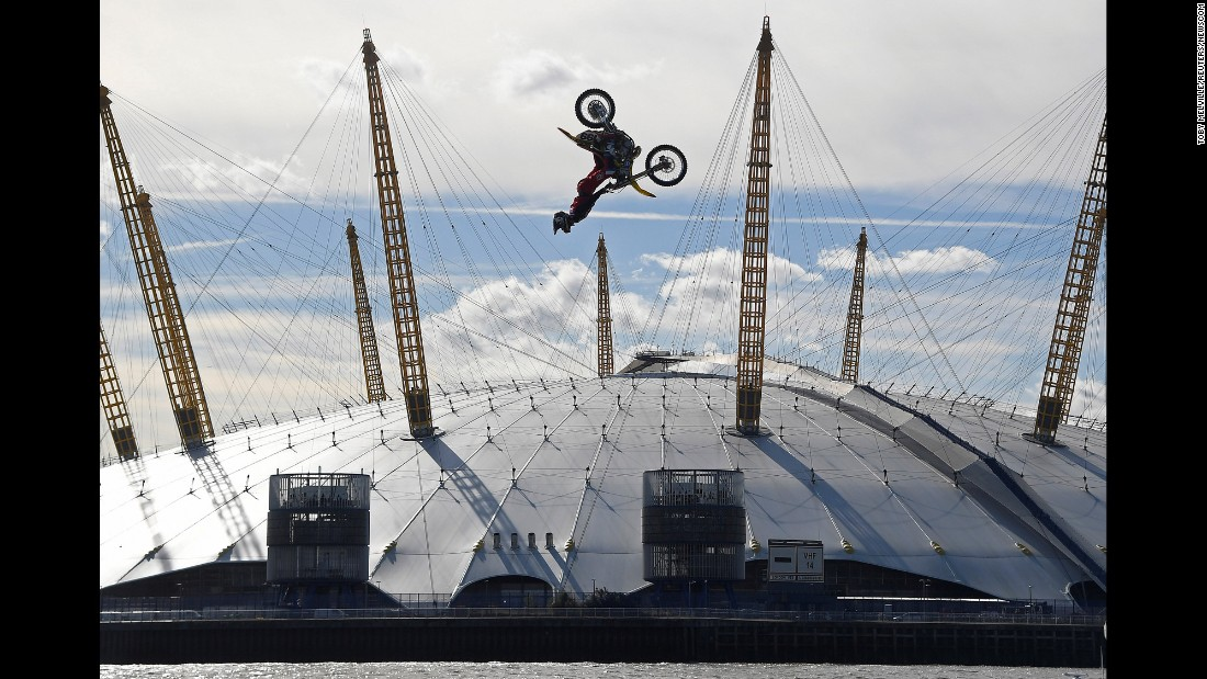 Action sports performer Travis Pastrana somersaults on his motorbike as he jumps between two barges on the River Thames in London, on Thursday, October 5.