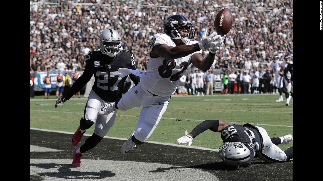 Baltimore Ravens tight end Benjamin Watson misses a pass in the end zone in front of Oakland Raiders free safety Reggie Nelson, left, during the first half of an NFL football game in Oakland, on Sunday, October 8.