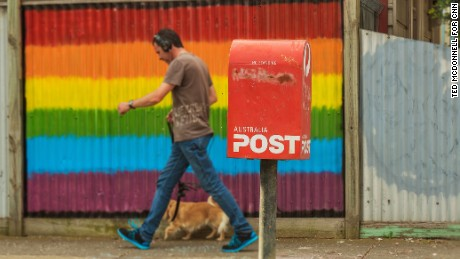 A man walk his dog past a Rainbow painted fence next to a post office box. Australians are not voting either Yes or No in the Same Sex Marriage Survey.