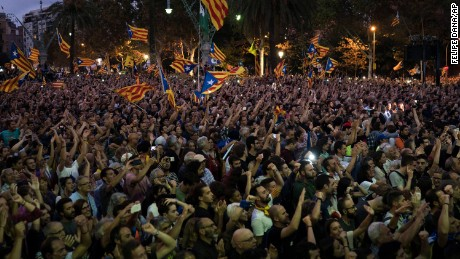 Pro-independence supporters watch Catalan President Carles Puigdemont's speech on a big screen in Barcelona.