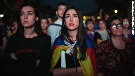 Pro-independence supporters react as they watch on broadcast screens outside the Parliament of Catalunya as the Catalan President Carles Puigdemont announces he will abide by the referendum results on October 10, 2017 in Barcelona, Spain.
