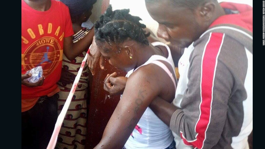 A female voter is held up after fainting in line at the School of Christ polling center in Weala, Margibi County. She had been waiting to vote since 5am in the morning. <br /><br />Credit: Local Voices Liberia/Emmanuel Tophic Degleh