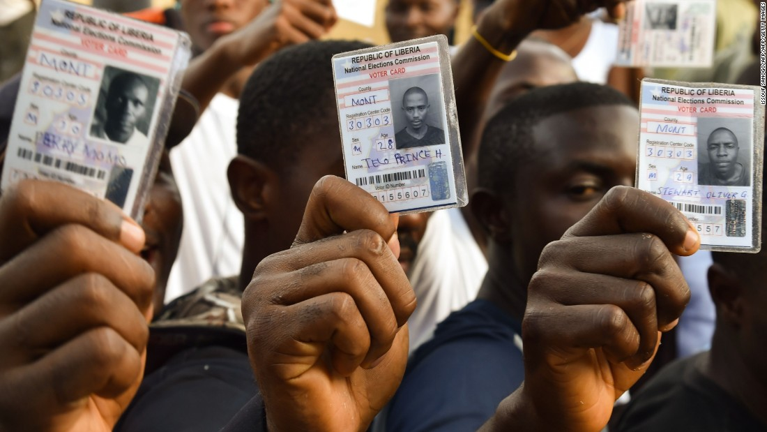 Voters in Monrovia, Liberia, hold their voting card prior to casting their vote for Liberia's presidential and legislative elections, at a polling station on October 10, 2017. It will be the first time since 1944 that one democratically-elected government will transition to another.