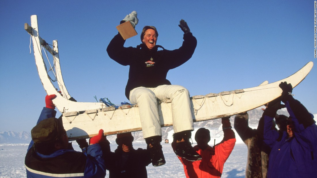 A winner is lifted atop a traditional dog sled after victory...