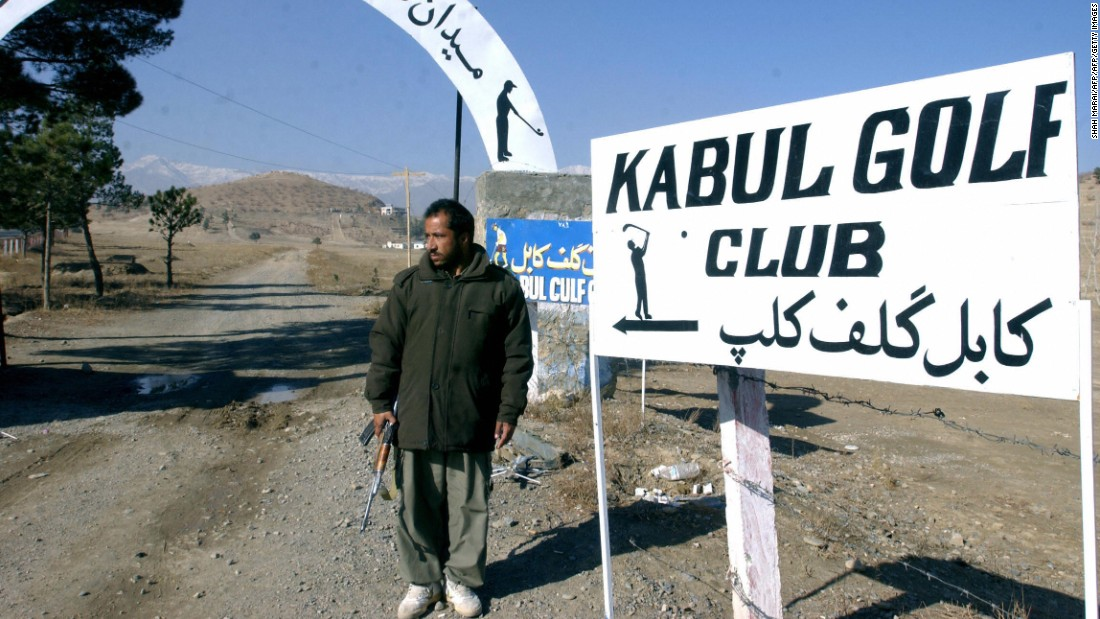"Kabul Golf Club describes itself as the ""best and only"" course in Afghanistan and promises ""golf with an attitude."" An armed security guard stands beside the entrance."